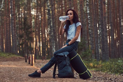 Tourist girl stopped to rest and drink water in the beautiful autumn forest.