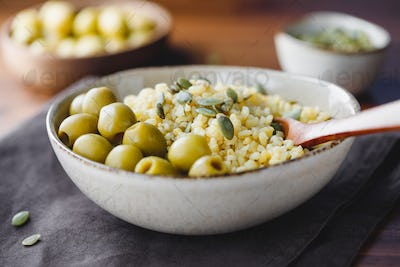 Bulgur with green olives and pepitas, healthy nutrition easy recipe from long-stored food