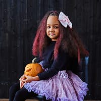 ittle girl dressed in trendy scary dress holds pumpkin while sitting on chair in dark house.