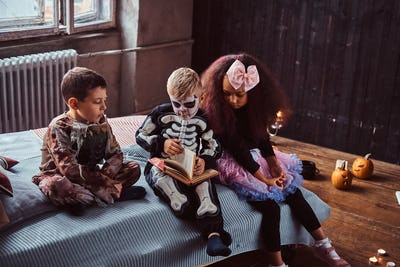 Three multiracial kids in scary costumes reading horror stories sitting on bed in an old house.