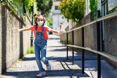 Child girl running outdoors wearing a protection mask against coronavirus during Covid-19 pandemic