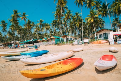 Canacona, Goa, India. Canoe Kayak For Rent Parked On Famous Palolem Beach On Background Tall Palm