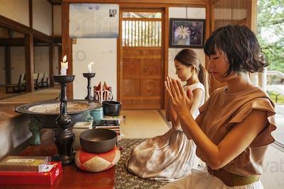Two Japanese women kneeling in Buddhist temple, praying.
