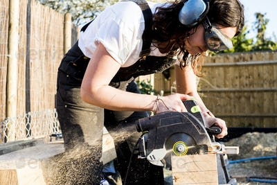 Woman wearing protective goggles and ear protectors holding circular saw, cutting piece of wood on
