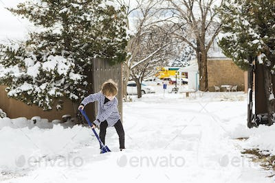 A six year old boy shoveling snow in driveway