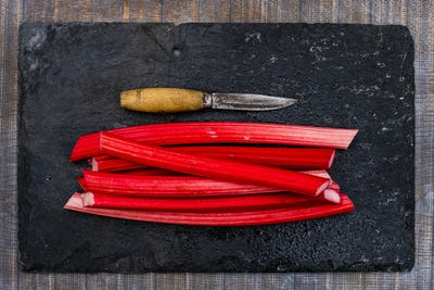 High angle close up of rhubarb stalks and knife on black slate.