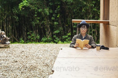 Japanese woman wearing glasses and hat sitting at a table outside Eco Cafe, reading book.
