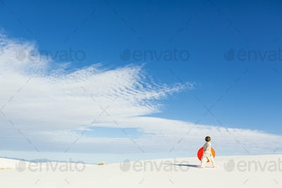 6 year old boy carrying an orange sled in a white undulating dune landscape.