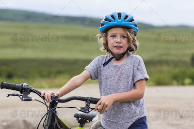 portrait of 5 year old boy holding his mountain bike