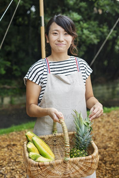 Smiling Japanese woman wearing apron standing outdoors, holding basket with fresh vegetables,