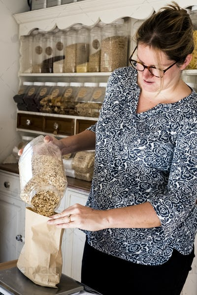 Woman standing in kitchen, pouring oats into paper bag.