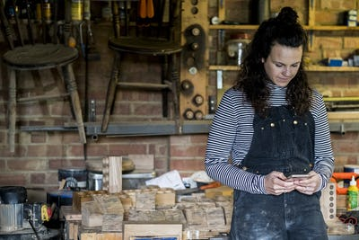 Woman with long brown hair wearing dungarees standing in wood workshop, using mobile phone.