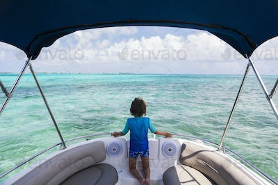 5 year old boy on a boat looking at the ocean