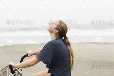 teen girl biking on sand at the beach, St. Simon's Island Georgia