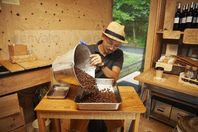 Japanese man wearing hat and glasses sitting in an Eco Cafe, pouring freshly roasted coffee beans