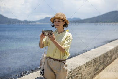 Japanese woman wearing hat standing by the ocean, taking picture with mobile phone.