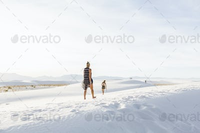 woman walking in the dunes, White Sands Nat'l Monument, NM