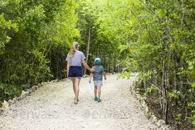 rear view of 13 year old sister and her 5 year old brother walking on nature path