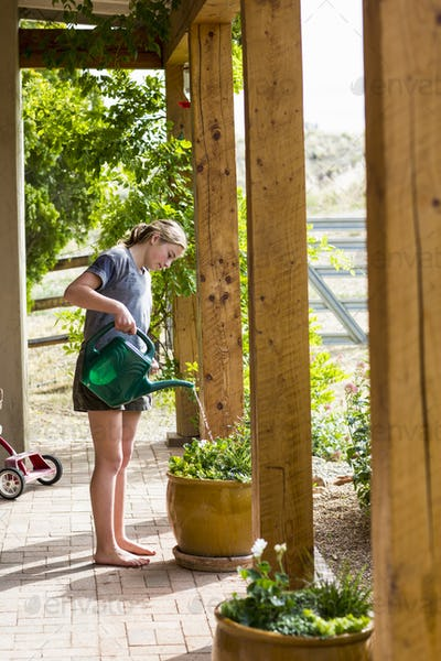 A teenage girl watering plants on a terrace.