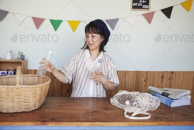 Japanese woman standing in a farm shop, sorting clear plastic bottles into basket.