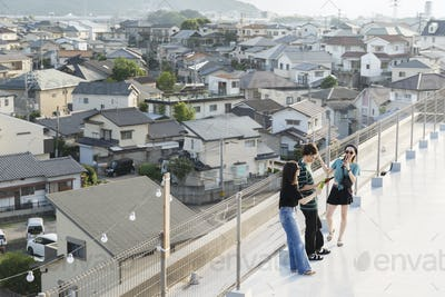 High angle view of group of young Japanese men and women standing on a rooftop in an urban setting.