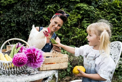 Woman and girl sitting at a table in a garden, feeding white chicken.