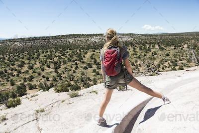 rear view of 13 year old girl hiker overlooking desert vista, Tsankawi Ruins, NM