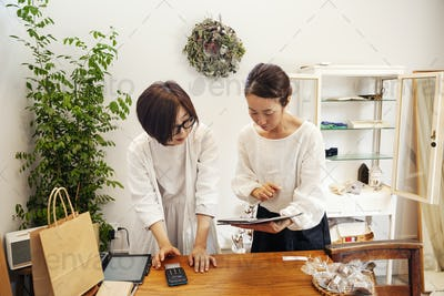 Two Japanese women standing in a small fashion boutique, looking at digital tablet.