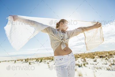 13 year old girl dancing with a shawl in the open space of white sand dunes.