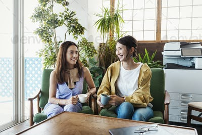 Two female Japanese professionals sitting in a co-working space, smiling at each other.
