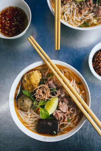 High angle close up of bowl of Bun Bo Hue with beef, crab balls, blood sausage and herbs.