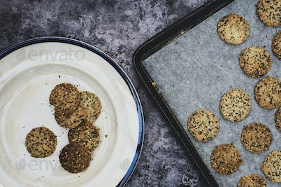 High angle close up of freshly baked seeded crackers on a plate and baking tray.