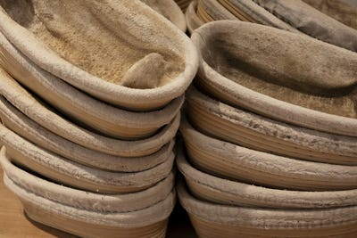 Close up of stacks of proving baskets in an artisan bakery.
