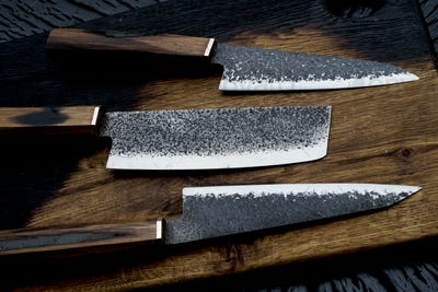 High angle close up of three handmade knives on wooden cutting board.