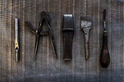 High angle close up of selection of saddle making hand tools.