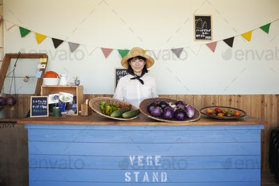 Japanese woman wearing hat standing behind counter in a farm shop, smiling at camera.