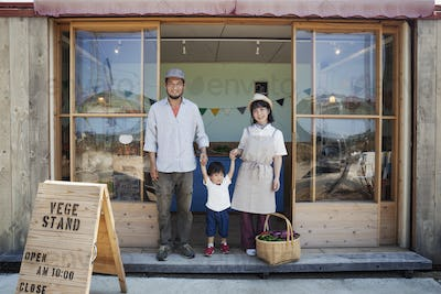 Japanese man, woman and boy standing outside a farm shop, holding hands, looking at camera.