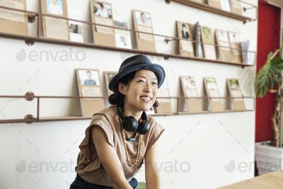 Female Japanese professional wearing Trilby hat and headphones sitting  in a co-working space.