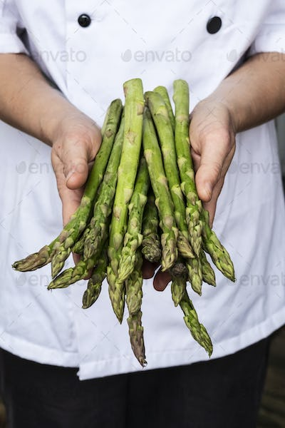Close up of chef holding a bunch of green asparagus.