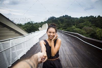 Smiling young woman standing on a bridge, holding man's hand.