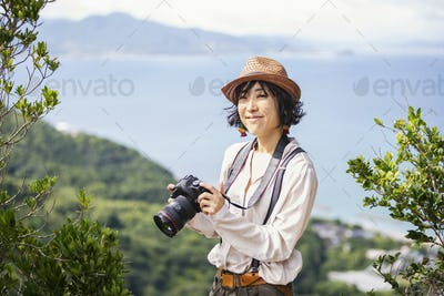 Japanese woman wearing hat and carrying backpack and camera standing on a cliff, ocean in the
