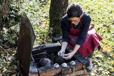 High angle close up of woman wearing red apron kneeling next to outdoor smoke fire pit, working on
