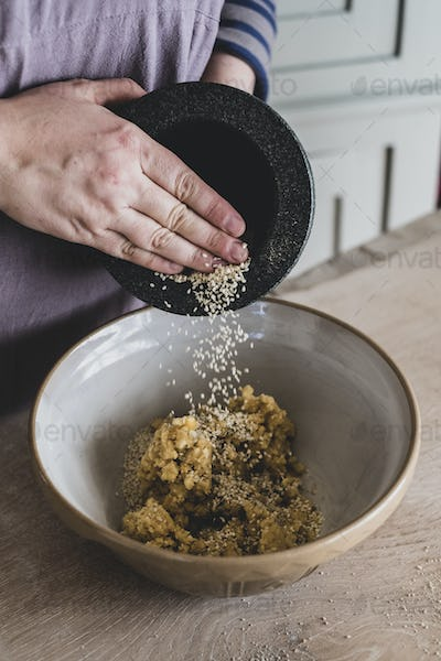 High angle close up of person adding sesame seeds to dough in a mixing bowl.