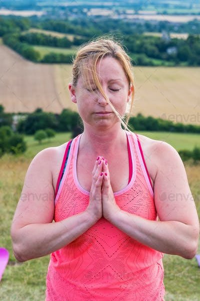 Mature woman taking part in a yoga class on a hillside.
