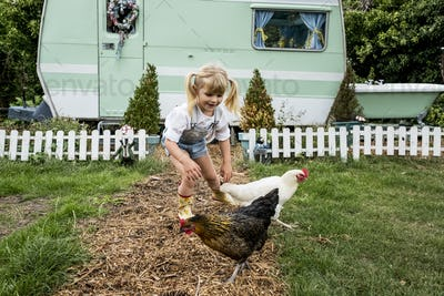 Blond girl with two chickens on a garden path, white and green retro caravan in background.