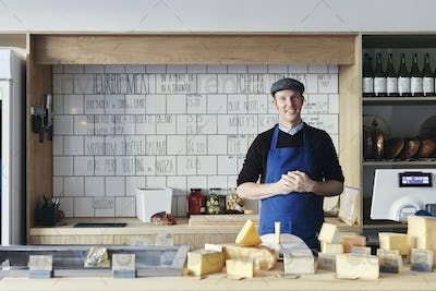 Portrait of cheesemonger behind counter arranged with a variety of cheeses