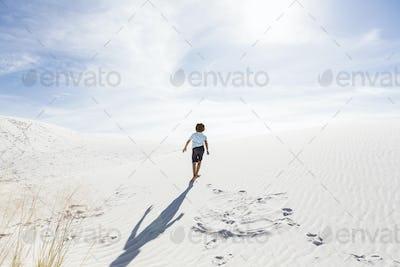 6 year old boy climbing sand dune