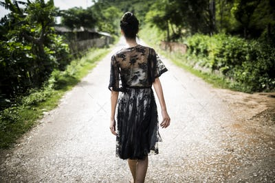 Rear view of woman wearing black lace dress walking down a rural country road.