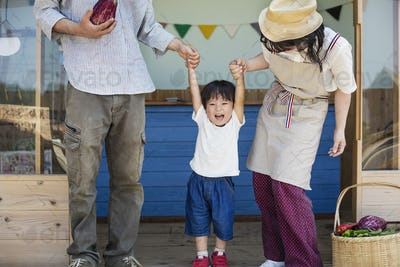 Japanese man, woman and boy standing outside a farm shop, holding hands.