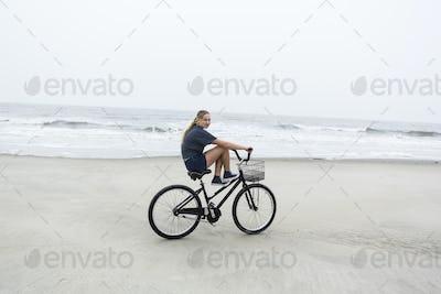 teen girl biking on sandy beach by the ocean, St. Simon's Island, Georgia